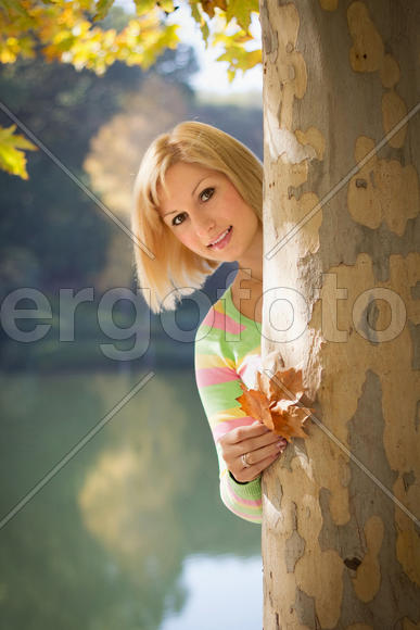 Smiling blonde girl in park with leaves in hands