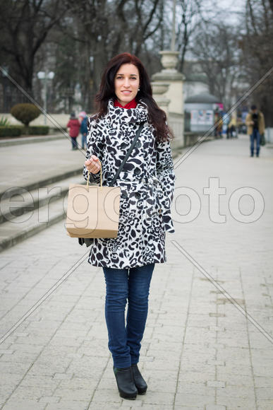 Young beauty woman in casual clothes with shopping bag walking through street
