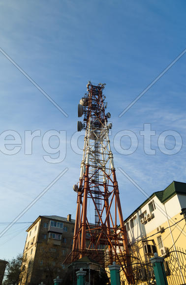 Communication tower against the bright blue sky with clouds