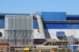 Big plant for processing scrap metal. Huge factory old metal refiner. Blue roof of the factory build