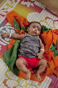 Indian baby lying on colorful mat in the village