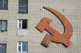 Emblem of the hammer and sickle on the wall of a house