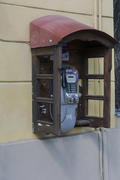 Phone booth on the wall of an apartment house in the city