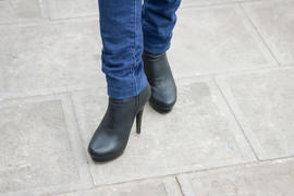 Girl's leg with black boots on a high heel. Street style