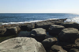 Rocks and sea meet in the bright sunlight in autumn