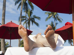 The person on vacation lies on a chaise lounge under an umbrella in beams of the tropical sun